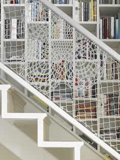 marisadobson:  Since both owners work in book publishing, there was a profound need for bookshelves integrated into the house. Manis masterminded staggered white built-ins, which she calls beehive shelving, that run along the stairs, the bottom openings shaped to the slant. The railing is made of white PVC-coated chain-link, woven into a lace-like pattern. From Design Brooklyn(October 2013). Read more.