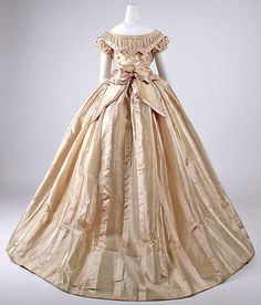 Satin-striped silk, French, ca 1865. Low bodice, tucker, bertha of tulle and piping, functional buttons; small puffed sleeves; pleated eliptical skirt, flat front panel. Stacked double bow trims waist in back. MET