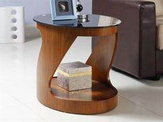 Jual Furnishings JF304 Curved Oval Lamp / Side Table in Walnut        Raise the level of style in your living room with the JF304 oval lamp table in walnut.      This modern, luxurious table from Jual Furnishings features piano black glass shelves and natural walnut veneer to ensure it becomes pride of place in your home.  Useful for placing your lamp and your small personal items, the good size top surface makes a practical storage area.