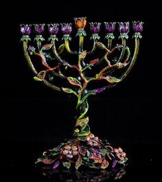 Jay Strongwater enamel and swarovski crystal menorah. Very ornate menorah featuring a central foliate and floral motif. Entire piece is made from metal with a multi colored enamel overlay. The base is comprised of leaves, flowers, and pedals which climb up the main stem splitting into nine branches. At the end of each branch is a flower in full bloom. Littered with Swarovski crystals throughout. Jay Strongwater plaque underneath base. CIRCA: Late 20th Century