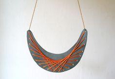 mittellange kette  grosser grauer lederanhänger mit orangefarbener seide bestickt  ergibt ein geometrisches muster
