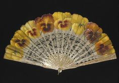 The leaf of this 1890-1900 fan carries the signature of Ronot-Tutin. He was a French fan painter who specialized in floral fan leaves. The top part of the leaf is painted silk gauze, with a panel of bobbin lace below. Although Ronot-Tutin has painted the pansies very realistically, their bright color and size were not in keeping with French tastes at the time. He may have made this fan for an English customer, or for someone who wanted a fan to match a particular dress.