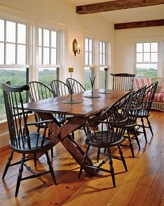 """""""Pinner writes I designed the dining room to look like a sun porch,"""" Blake explains. She added a small seating area at one end of the room and used vintage ticking to cover the pillows and cushions. Custom-made Windsor chairs surround the circa 1860 sawbuck table.  Beautiful"""
