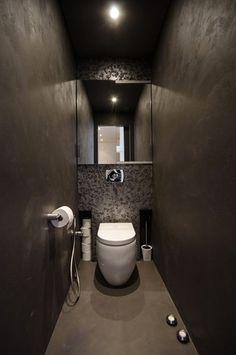 Déco toilettes design avec murs en stuc gris taupe, papier métallisé gris cuvette suspendue blanche, au sol un béton ciré couleur taupe