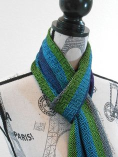 Handwoven scarf in blue, turquoise, green and gray, with black diamonds.