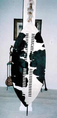 """ZULU WAR SHIELD SHAKA STYLE  """"inGobamakhosi"""" ( Bender of Kings) Regiment  King Cetshwayo 1873  6' 8 inches from top of Center-pole to floor  Skin shield 4'11""""  Center-pole removable as used on the march.  Price: $785.00"""