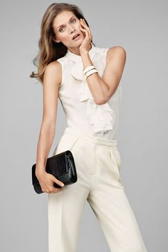 Ruffled silk sleeveless blouse, beige high-waisted suit pants, and a black leather shoulder bag as an accent.│H&M Modern Classics.