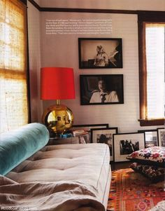 love the pop of red in the lamp and the gold base. especially like the large selection of black and white photos leaning against the wall