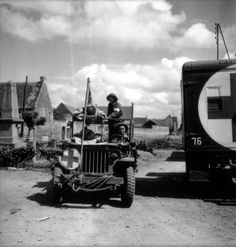 Jeep ambulance of the 23rd Field Ambulance, 9th Infantry Brigade, 3rd Canadian Infantry Division driven by Private L.E McKeating, carries two stretcher cases. Private L.F. McCadam stands to care for the patients. Picture taken on the 27th of june 1944, with the Basly war memorial in the background. To the right is an ambulance carrying a white 76 on a black background identifying a vehicle of the 22nd Field Ambulance Company, 8th Infantry Brigade.