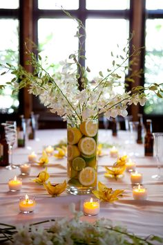 The freshness of the lemons and limes says patio party. Staying with the citrus theme, float an orange candle on top instead of the flowers and use orange accent tea candles.