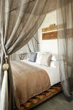 calm, rustic bedroom, wooden beam bed simple luxury details like wooden art carvings, silver tassels around sheer linen curtains
