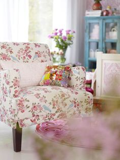 Pretty floral chair with beautiful blue cupboard in the background