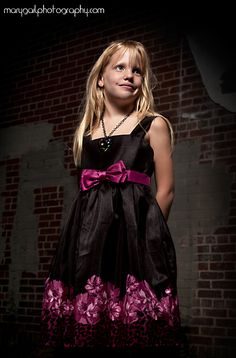 child portrait child photography little girl pink flowers black dress blonde hair brick wall