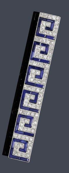 An Art Deco platinum, diamond and sapphire brooch, circa 1925. The rectangular diamond-set bar with sapphire Greek key motifs mounted in platinum.