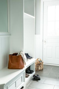 1146a25752b White and gray mudroom boasts a built-in bench accented with shiplap trim  next to an open locker fitted with shoe shelves alongside a gray tiled  floor.