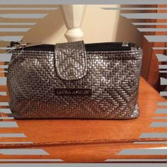 Laura Ashley Makeup Bag This little silver bag is 7 1/2 by 4 and is perfect to Cary anything inside your larger bag. Inside has clear plastic zip compartments for easy vision and will keep things from spilling. This is fantastic for the working girl! Laura Ashley Bags