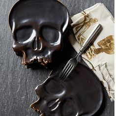 "Halloween Skull Plates... no bones about it, these skull plates will be the life of the party. Their delightful features include a generous cranium for holding appetizers and desserts & a fiendish gap-toothed grin (hand cast from durable stoneware; glazed in subtly iridescent graphite gray with lightly distressed details; microwave & dishwasher safe; 7 1/4"" x  6 1/4"" overall; set of 4; 51.95) 