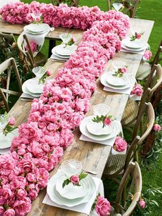 What a spectacular pink centrepiece with faux pink peonies. Buds were also entwined on each glass, within each napkin and tied a wreath with a blossom onto each chair.