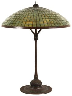 "24 in. Tiffany Studios Parasol Table Lamp. Large saucer shaped shade has a 12 row geometric pattern in dark mottled green glass, a 0.5 in. bronze flat rim and 1 7/8 in. aperture, shade measures 6.5 in. high; shade number 1520 and is signed ""Tiffany Studios New York"". On a bronze ""Parasol"" style base with wide platform and long stem base having a crossed ribbed design, top with a 2 in. pierced bronze heat cap; signed ""Tiffany Studios New York, 374""."