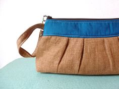 Pleated Brown Linen Clutch with Peacock Blue Accents  This pleated wristlet will seamlessly take you from work to play.