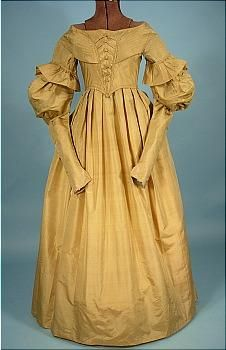 "Circa late 1830s Dress of Golden Silk with Matching Pelerine! This dress has it all -   pleating, ruffles, stitched-down gigot sleeves, tight lower sleeves, ""V"" at waistline at front, cording, and ""corset-like"" detailing at front bodice."