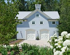 Garages designed as coach houses and horse barns have an Old World charm that completes a home and garden. The simple and elegant structure, with square windows, carriage style doors, board and batten siding, and a metal roof illustrate the charm of simple materials... Neat way to turn an old barn into a garage....