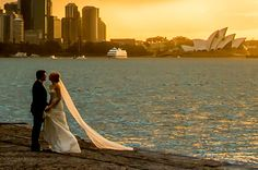 """The bride was wearing a pretty long, flowing gown and was trying to prevent it from getting wet, her husband was trying to help her and combat the epic wind that was throwing the dress around. Wedding Couple Photos, Wedding Couples, Sydney Wedding, Fantasy Wedding, Getting Wet, Wedding Venues, Gowns, Bride, Wedding Dresses"