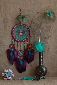 Detailed dreamcatcher is made in the style of Moroccan boho. This is my authors dreamcatcher. It combines four different colours: violet, light lilac, orange, turquoise(+green).The design features unique woven web. I used natural materials: metal hoop, cotton thread, hand-painted wooden and paper beads, rooster and goose feathers dyed. Dream catcher is a excellent decoration for your home, and also an excellent gift for family members or friends.  Size: diameter of the hoop 7 (18,7cm) length…