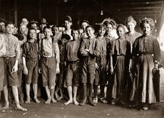 """January 1909. Augusta, Georgia. """"Noon Hour. Workers in Enterprise Cotton Mill. The wheels are kept running through noon hour (which is only 40 minutes) so employees may be tempted to put in part of this time at machine if they wish."""" Photograph and caption by Lewis Wickes Hine"""