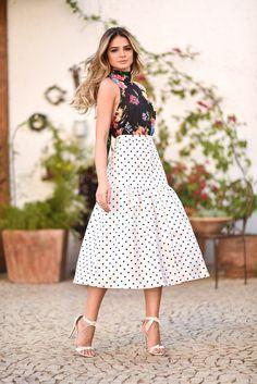 Look da Thássia Naves com mistura de estampas: saia midi de poá branca e preta, blusa de frente única estampada com flores e sandália de salto