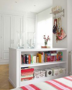 Love the idea of using a shelf to divide a space.  You could use a big-box shelf and add moulding around it for a built-in feel!