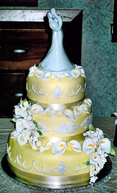 Yellow tinted buttercream with yellow ribbon borders, fondant scrolls and medallions. Calla lilies complete the design.