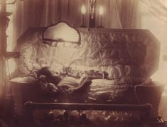 A matt silver gelatin print dating from the 1920's, or shortly afterwards, showing a young girl lying in a satin-lined casket with drop-panel side. An electric light with a pleated lampshade is situated directly above her face, bathing the girl in an eerie glow. Two further light bulbs, in the shape of candle flames, are situated either side of a crucifix behind the casket. Another crucifix can just be seen on the left-hand edge of the image.  Photographer almost certainly American in…