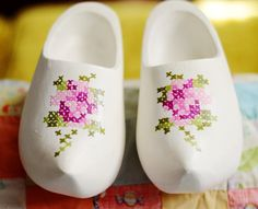 Inspiration: painted cross stitch clogs by Maize Hutton - a pair of unfinished wooden clogs, draw up a rose (or other pattern) on graph paper to fit, trace it on the clog and reverse it for the other foot.