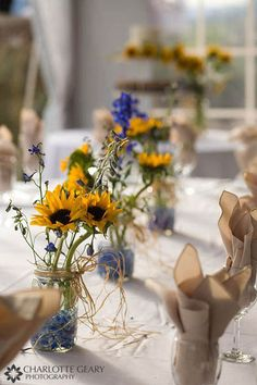 Sunflower centerpieces in mason jars - could use other vases/candle holders and fill bottom with shells/sand instead of water/water beads
