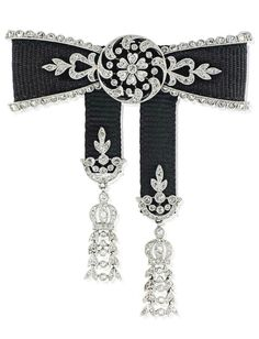 CARTIER - A BELLE EPOQUE DIAMOND BOW BROOCH, CIRCA 1910. The central millegrain-set rose-cut diamond flowerhead motif within a similarly-set scrolling border with foliate accents to either side, mounted on a black grosgrain ground, with further diamond borders, suspending two ribbons with diamond tassel terminals, single pin fitting, 4.9cm, signed Cartier, Paris. #Cartier #BelleÉpoque #brooch