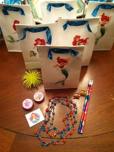 Little Mermaid's Sweets Under The Sea Party - goodie bags made with white lunch bags, sparkly ribbon & Ariel stickers.