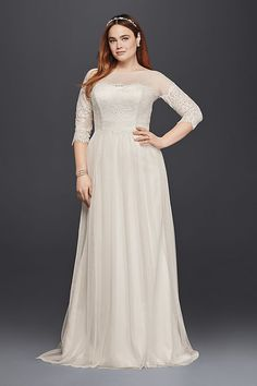 Carefully placed lace gives the illusion of an off-the-shoulder neckline on this lace plus size wedding dress. A soft tulle skirt and sheer sleeves make it effortless.  Galina, exclusively at David\'s