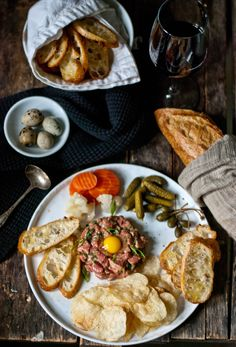 """Steak Tartare dinner! Quail egg, warm kettle chips, toasty Crostini, cornichons and other """"pickled things"""", caper berries. #happybelly"""