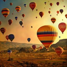 The oragne hue of the sunrise against the hot air balloons of Cappadocia, Turkey - A perfect combination!