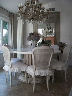 White cane backed chairs and ruffled seat covers are romantic.