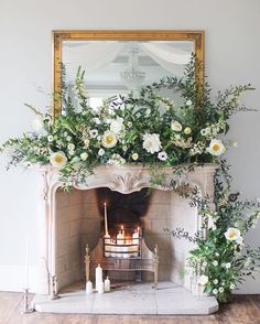 Incredibly exquisite fireplace mantel floral arrangement. Oversized, white roses and flowers, candles instead of wood.