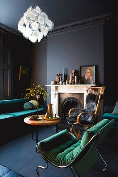 Black living room with teal sofa and modern light fixture