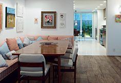 O assoalho de demolição é um dos atrativos dessa sala de jantar. Junto com o sofá, cheio de almofadas, ele oferece calor ao ambiente  Nelson Kon / Casa e Jardim