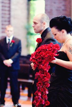 Finnish bride with a black dress and an incredible cascading red rose bouquet from Inked Weddings.