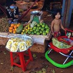 Humble fruit shop in Mondulkiri, Cambodia - While traveling towards the highlands of Cambodia and the town of Sen Monorom i stopped in one village on the road to grab some fresh fruit, the moment i set my foot on the red soil i was greeted by this amazing scene, it was pure luck that my iPhone was in my hand so i managed to capture the moment before the little girl ran in the back of the shop.