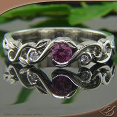 Half Bezel Wrap Mounting for a Pink Sapphire with (2) 1.5mm Round Diamonds (0.025ctw) set in pierced vine curls that wrap over each other and around the center stone with beautiful carved leaves (Green Lake Jewelers)