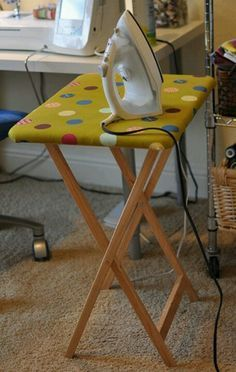 TV tray padded & covered with fabric ...makes an ironing table for pressing  as you sew .