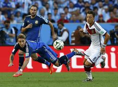 Germany's Mesut Ozil (R) fights for the ball with Argentina's Lucas Biglia (front) and Enzo Perez during their 2014 World Cup final at the Maracana stadium in Rio de Janeiro July 13, 2014