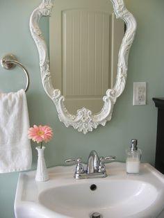 White hand towel, silk gerbera in milk glass vase, white soap, white mirror. Staging Bathrooms | markatosservices